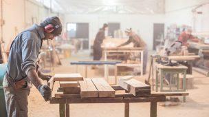 Homem-trabalhando-marcenaria-cortando-madeira-num-local-aberto-marcenaria-grande-homens-trabalhando-aofundo-ao-fundo