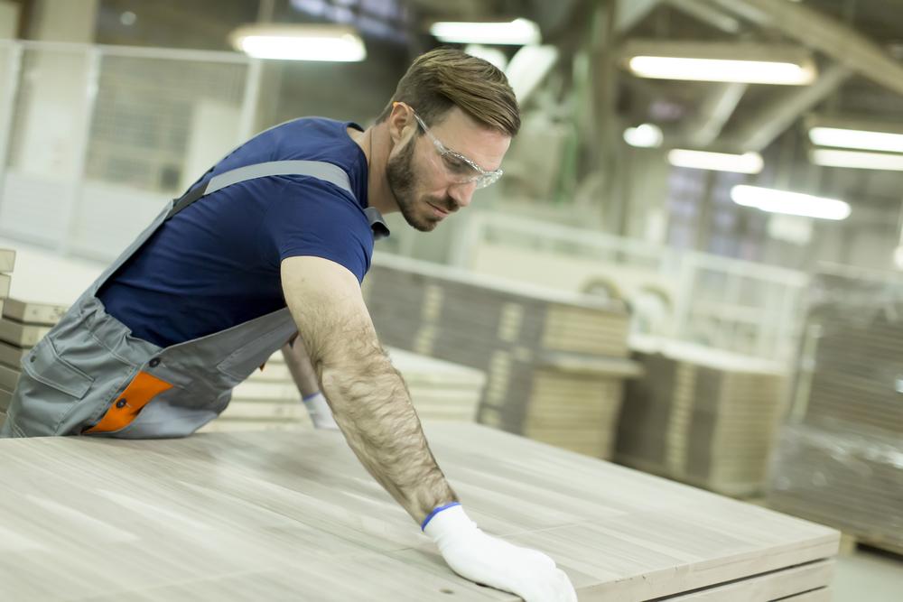 Marceneiro-homem-trabalhando-marcenaria-medindo-madeira-na-fabrica-de-moveis