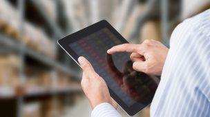 Homem-mexendo-no-ipad-tablet-trabalhando-com-camisa-social-no-estoque-da-fabrica-digitando-no-tablet-ipad-tocando-na-tela-do-tablet-ipad