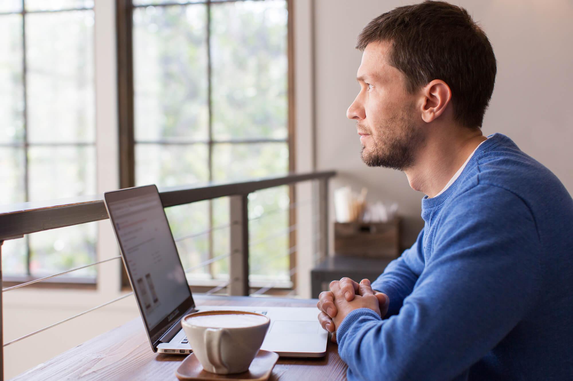 Homem-na-frente-nafrente-do-computador-trabalhando-bebendo-café-em-casa-emcasa-pensando-em-melhorar-o-sistema-osistema-de-gestão-da-fabrica-trazendo-benefícios-e-melhorias-na=fábrica-de-móveis