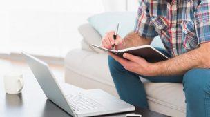 Homem-calculando-fazendo-contas-trablhando-na-frente-do-computador-notebook-com-celular-ao-lado-do-computador-sentado-no-sofá-da-sala-escritório-trabalhando-para-melhorar-gestão-de-compras-decompras-para-sua-fábrica-de-móveis