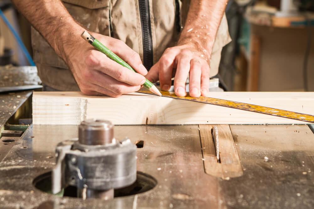 Pessoa-calculando-numa-mesa-somando-gastos-e-lucros-homem-trabalhando-calculando-os-custos-do-seu-próprio-negócio-com-caneta-e-fita-métrica