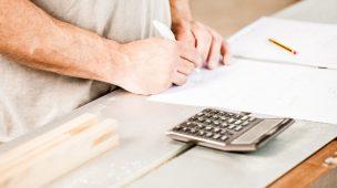 Contas-a-pagar-receber-gestão-financeira-calculando-finanças-da-empresa-administrando-melhor-saindo-do-vermelho-aprendendo-a-melhorar-administração-da-marcenaria-calculadora-papel-caneta-sendo-utilizadas-no-calculo