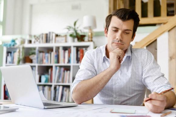 Homem-pensando-na-frente-do-computador-tendo-ideias-negocio-próprio